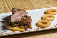 Beef steak with chips and onion rings Royalty Free Stock Photography