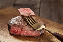 Beef steak. Cooked to medium rare on wooden background Royalty Free Stock Photos