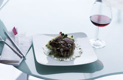 Beef steak with creamy sauce. Luxurious restaurant meal served with a glass of red wine Royalty Free Stock Images