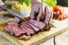 Beef steak cut on chopping board. Cutting of grilled beef steak on chopping board stock photo