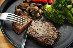 Beef steak is cut with knife and fork, with vegetables like broccoli, mushrooms and tomatoes, low carb diet dinner on a dark gray. Plate, selected focus, narrow royalty free stock photos