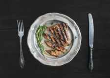 Beef steak cut into pieces with rosemary, knife and fork Royalty Free Stock Images