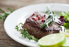 Beef steak. With fresh herbs and red pepper Stock Photography