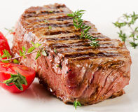 Beef steak with fresh herbs on a  white plate . Stock Photos