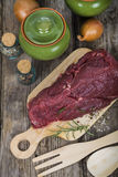 Beef Steak with fresh herbs on wooden board. Stock Photos