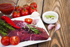Beef steak. Fresh beef steak on plate with aromatic spices and sauce on a wooden background Stock Photo