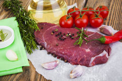 Beef steak. Fresh beef steak on plate with aromatic spices on a wooden background Royalty Free Stock Image