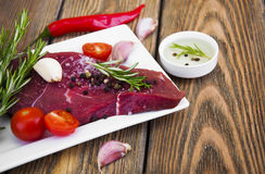 Beef steak. Fresh beef steak on plate with aromatic spices on a wooden background Stock Images