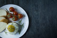 Beef steak with fried egg in spices. Decorated with rosemary, fresh cherry and slices of bread. Filed on a white plate. Dark stock photography