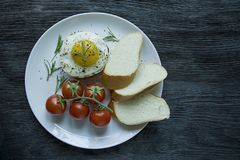 Beef steak with fried egg in spices. Decorated with rosemary, fresh cherry and slices of bread. Filed on a white plate. Dark stock images