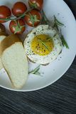 Beef steak with fried egg in spices. Decorated with rosemary, fresh cherry and slices of bread. Filed on a white plate. Dark stock photo