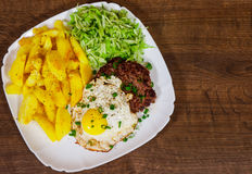 Beef Steak with fried egg, vegetables salad and potato in a white plate on wooden table Royalty Free Stock Photo
