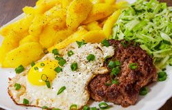Beef Steak with fried egg, vegetables salad and potato in a white plate on wooden table Royalty Free Stock Image