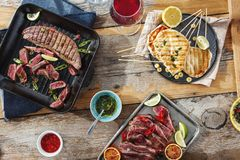Beef steak grill chicken steak grill wooden table sauces red win. Beef steak grill and chicken steak grill on wooden table with sauces and red wine on sunny day royalty free stock photos