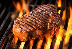 Beef steak on the grill. With flames royalty free stock photography