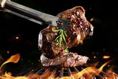 Beef steak on grill. Isolated on black background Stock Images