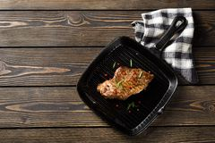 Beef steak on grill pan on a wooden table Stock Image