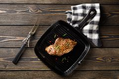 Beef steak on grill pan on a wooden table Royalty Free Stock Images