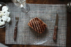 Beef steak grilled on a glass plate. Glass of wine, vegetables Stock Photo