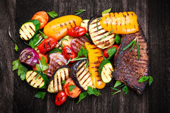 Beef steak and Grilled vegetables. On cutting dark board background Stock Photo