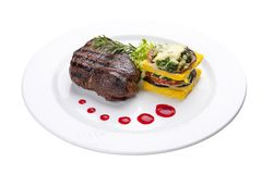 Beef steak with grilled vegetables and an omelette. On a white plate royalty free stock images