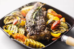 Beef steak with grilled vegetables in skillet Stock Images