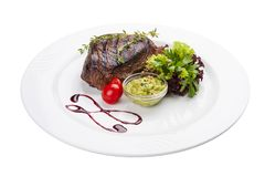 Beef steak with Guacamole sauce. On a white plate stock images