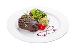 Beef steak with Guacamole sauce. On a white plate royalty free stock photo