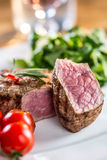 Beef Steak. Juicy beef steak. Gourmet steak with vegetables and glass of rose wine on wooden table Stock Image