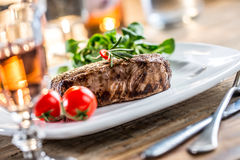 Beef Steak. Juicy beef steak. Gourmet steak with vegetables and glass of rose wine on wooden table Stock Photo