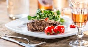 Beef Steak. Juicy beef steak. Gourmet steak with vegetables and glass of rose wine on wooden table royalty free stock image