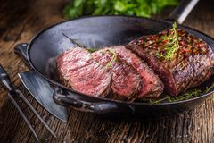 Beef steak. Juicy medium Rib Eye steak slices in pan on wooden board with fork and knife herbs spices and salt Royalty Free Stock Photo