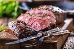Beef steak. Juicy medium Rib Eye steak slices on wooden board with fork and knife herbs spices and salt.  Royalty Free Stock Image