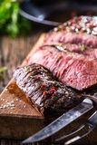 Beef steak. Juicy medium Rib Eye steak slices on wooden board with fork and knife herbs spices and salt.  Stock Image