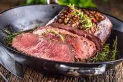 Beef steak. Juicy medium Rib Eye steak slices in pan on wooden board with fork and knife herbs spices and salt.  Royalty Free Stock Photography