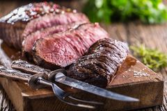 Beef steak. Juicy medium Rib Eye steak slices on wooden board with fork and knife herbs spices and salt.  Stock Images