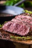 Beef steak. Juicy medium Rib Eye steak slices on wooden board with fork and knife herbs spices and salt.  royalty free stock photo