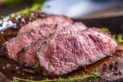 Beef steak. Juicy medium Rib Eye steak slices on wooden board with fork and knife herbs spices and salt Royalty Free Stock Photos