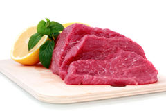Beef steak on meat hardboard with green leaf and. Lemon. Isolated stock photo