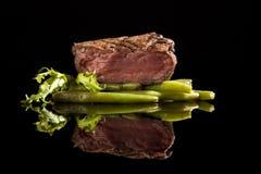 Beef steak medium rare on black background. Beef steak with salad and beans on black background stock images