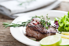 Beef steak medium rare. Beef steak with fresh herbs and red pepper Royalty Free Stock Photography