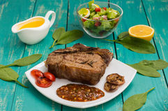 Beef steak medium rare on the grill with barbecue sauce. wood background Stock Image