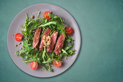 Beef steak medium, Ruccola salad with tomatoes and walnuts,gray plate. Blue background,copy space Royalty Free Stock Photos