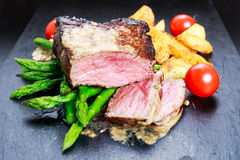 Beef steak Mignon cooked with Asparagus, potatoes, garlic and tomatoes. Served on blue stone board royalty free stock images