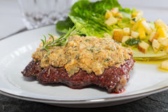 Beef steak with mustard herb crust and romaine lettuce hearts wi Stock Photos