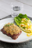 Beef steak with mustard herb crust and romaine lettuce hearts wi Royalty Free Stock Photos