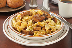 Beef steak on noodles. A bowl of beef tips with mushroom gravy on buttered noodles royalty free stock photography