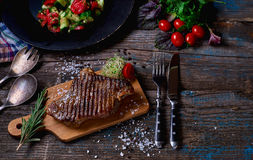 Beef steak. Piece of Grilled BBQ beef marinated in spices and herbs on a rustic wooden board over rough wooden desk with a copy sp Royalty Free Stock Photo