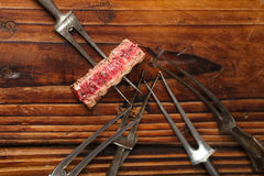 Beef steak piece on vintage meat fork Royalty Free Stock Photo