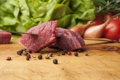 Beef steak pieces on a wooden board, close up. Wooden cutting board with pieces of beef, peppercorns and vegetables Royalty Free Stock Image